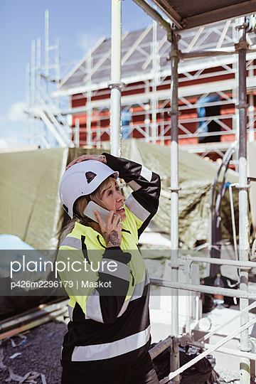 Female builder talking on mobile phone standing at scaffolding - p426m2296179 by Maskot