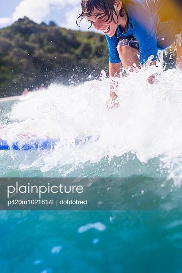 Boy surfer riding the wave - p429m1021614f by dotdotred