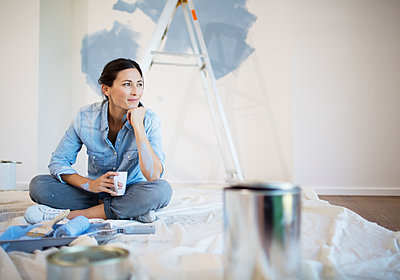 Woman relaxing with coffee among painting supplies - p1023m1146341 by Paul Bradbury