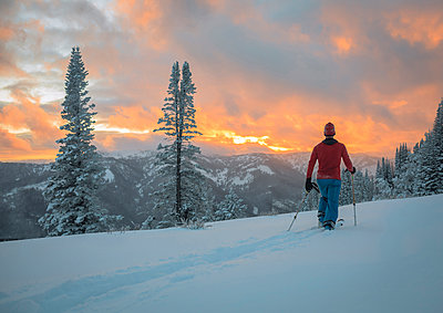 Rear view of male hiker skiing on snowy field during sunset - p1166m1532265 by Cavan Social