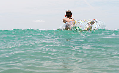 relaxed white boy swimming in a float in the sea enjoying calm waves in summertime. Backwards horizontal photo - p1166m2213137 by Cavan Images