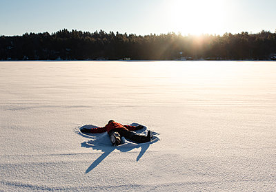 Child making a snow angel in an open snowy field in the morning sun. - p1166m2255297 by Cavan Images