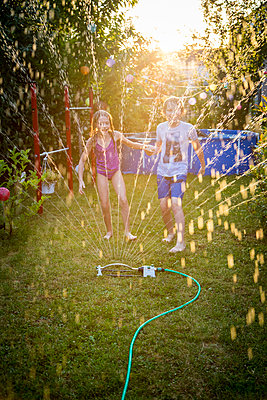 Brother and sister having fun with lawn sprinkler in the garden - p300m2023488 by Sandra Roesch