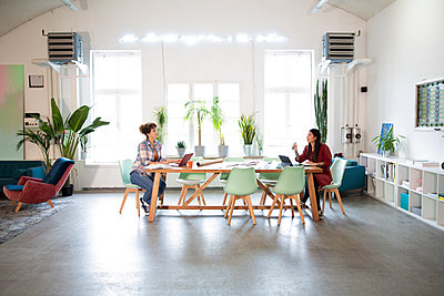Two women working at table in modern office - p300m2114244 by Florian Küttler