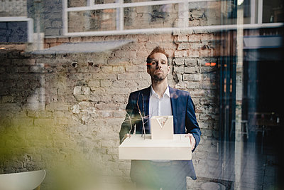 Portrait of businessman holding architectural model - p300m2131921 by Gustafsson