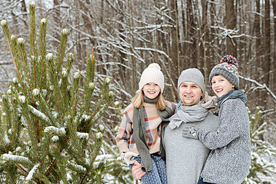 Portrait of happy father with two children at a fir tree in winter - p300m2166434 by Ekaterina Yakunina