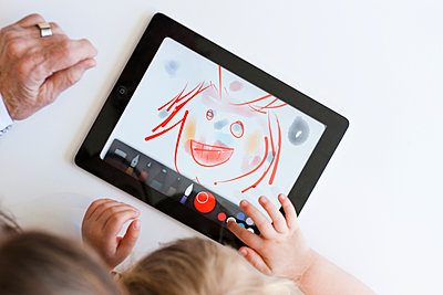 Grandmother and granddaughter drawing on digital tablet - p312m1075899f by Peter Rutherhagen