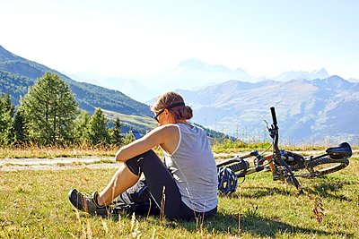 Female mountain biker sitting in mountain landscape reading smartphone texts, Aosta Valley, Aosta, Italy - p429m1125892f by Violeta Beral
