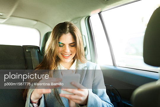 Portrait of smiling young businesswoman sitting on backseat of a car looking at cell phone - p300m1587778 von Valentina Barreto