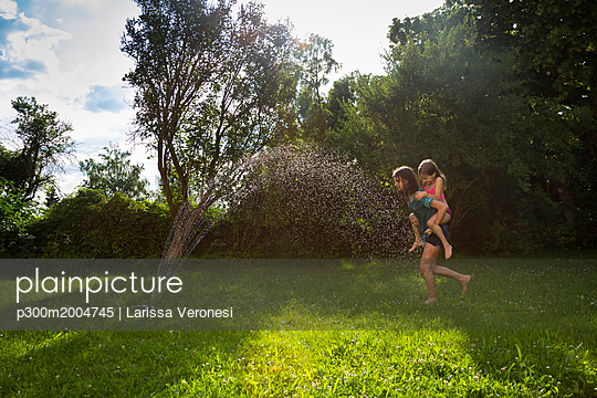 Girl giving her little sister a piggyback ride in the garden - p300m2004745 von Larissa Veronesi