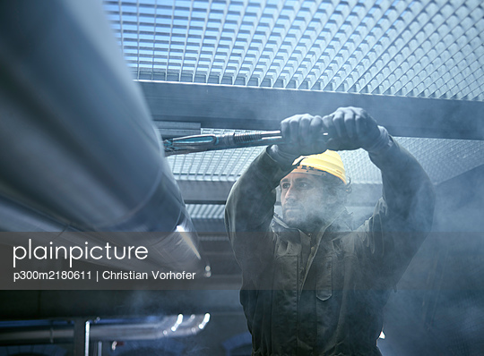 Technician with yellow helmet, fixing piepwork - p300m2180611 by Christian Vorhofer