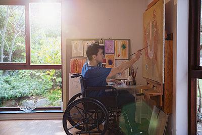 Male artist in wheelchair painting in art studio - p1023m2073956 by Tom Merton