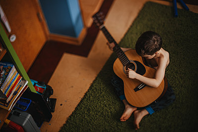 a boy plays his guitar quietly in his room - p1166m2094536 by Cavan Images