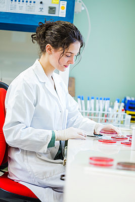 Young lab technician working with agar plates - p300m1023419f by Dieter Schewig