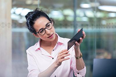 Female entrepreneur with eyeglasses holding solar model at office - p300m2265996 by Florian Küttler