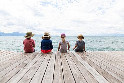 Four children sitting on boardwalk - p756m1464814 by Bénédicte Lassalle