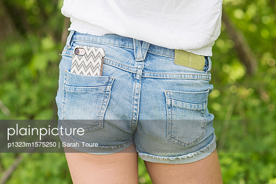 denim shorts and mobile phone - p1323m1575250 von Sarah Toure