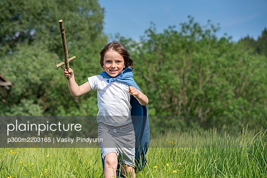 Playful boy wearing cape holding toy sword while running on grassy land - p300m2203165 by Vasily Pindyurin
