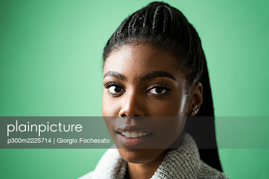 Smiling young woman against green background in studio - p300m2225714 by Giorgio Fochesato