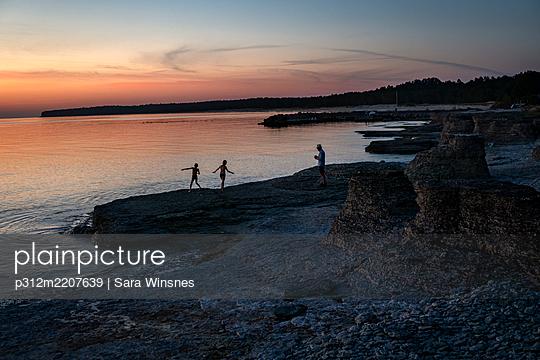 People at sea at sunset - p312m2207639 by Sara Winsnes