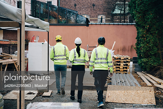Rear view of male and female engineers walking at construction site - p426m2295963 by Maskot