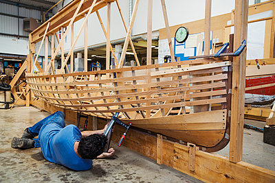 Man lying on floor in a boat-builder's workshop, working on a wooden boat hull. - p1100m1490075 by Mint Images