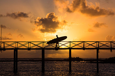 silhouette of a man carrying a surfboard on cloud nine bridge - p1166m2141108 by Cavan Images