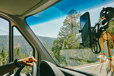 Young man driving on highway through Yosemite National Park. - p1166m2202133 by Cavan Images