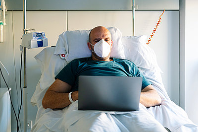 Patient wearing face mask working on laptop while sitting on bed at hospital - p300m2243602 by Jose Luis CARRASCOSA