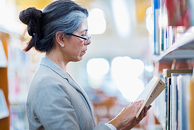 Older Hispanic woman reading book in library - p555m1414239 by Marc Romanelli