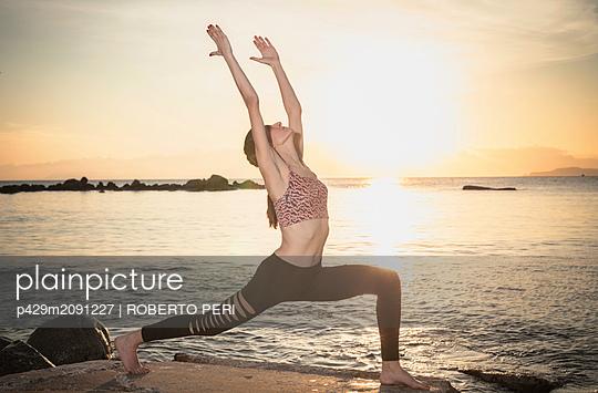 Woman practising yoga at seaside - p429m2091227 by ROBERTO PERI