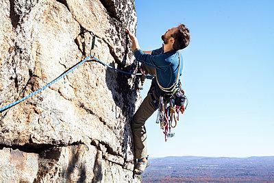 Man rock climbing against clear sky - p1166m1231469 by Cavan Images