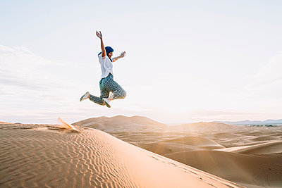 Happy woman jumping at Merzouga desert against sky - p1166m1530117 by Cavan Images