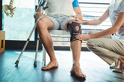 Female physiotherapist examining his patient's knee - p1315m1199693 by Wavebreak