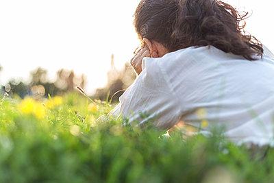Junge Frau liegt entspannt im Park - p1396m1481204 von Hartmann + Beese