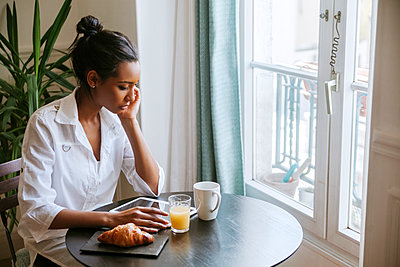 Young woman using digital tablet at breakfast table - p300m1140719 by Zeljko Dangubic