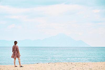 Greece, Rear view of woman looking at mount Athos across sea - p300m2131756 by Borislav Zhuykov