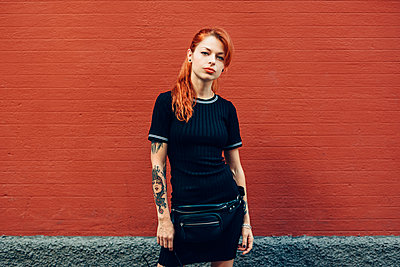 Portrait of red-haired tattooed woman standing at a brick wall - p300m2132037 by Javier Sánchez Mingorance