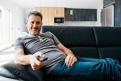 Smiling man holding TV remote while sitting on sofa at living room - p300m2266594 by Josep Rovirosa