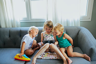 Kids on sofa using tablet - p312m1556826 by Anna Rostrom