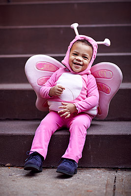 Mixed race girl wearing pink butterfly Halloween costume on staircase - p555m1413162 by Granger Wootz