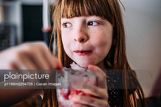 Happy young girl enjoying a home made snow cone - p1166m2294705 by Cavan Images