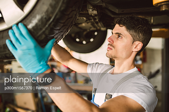Mechanic working on the underbody of a car in a workshop - p300m1587370 von Ramon Espelt