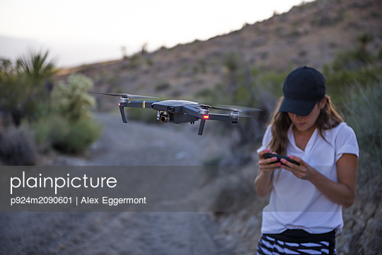 Woman operating drone (unmanned aerial vehicle) on rural dirt track - p924m2090601 by Alex Eggermont
