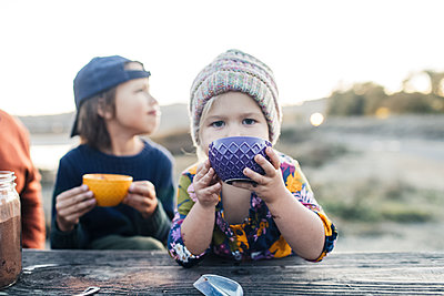 Adorable girl with brother drinking hot cocoa by woodden table at twilights - p1166m2095149 by Cavan Images