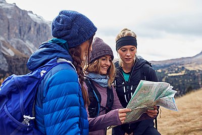 Three young women hiking in the mountains looking at map - p300m1562608 by Philipp Nemenz