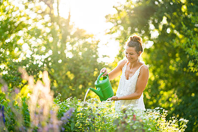 Young woman watering flowers in springtime garden - p300m2264666 by Annika List