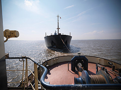 Tugboat pulling ship in ocean - p429m726957f by Monty Rakusen