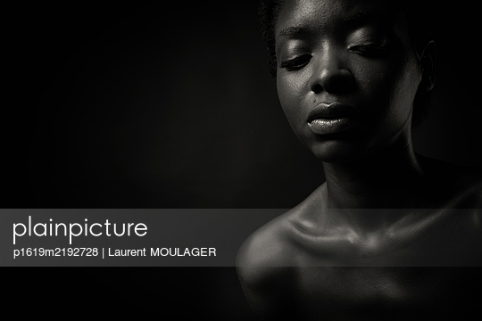 Black and white portrait of a young black woman eyes closed  - p1619m2192728 by Laurent MOULAGER