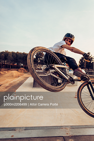 Man wearing helmet riding bicycle on ramp against sky during sunset - p300m2206499 by Aitor Carrera Porté